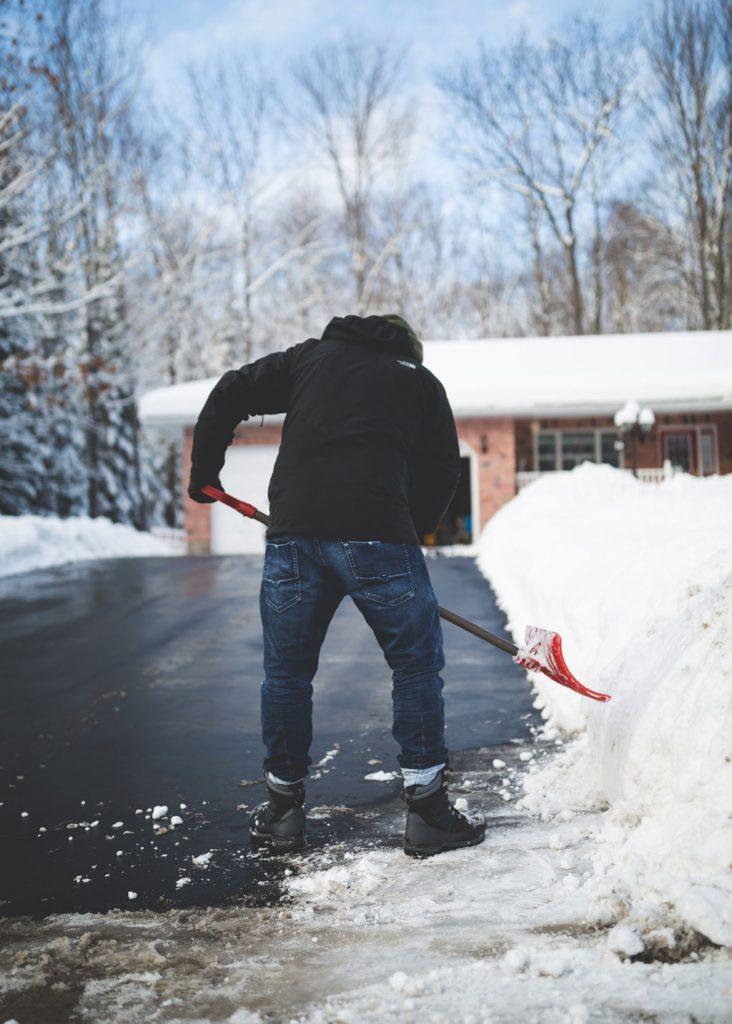 Schnee schippender Mann